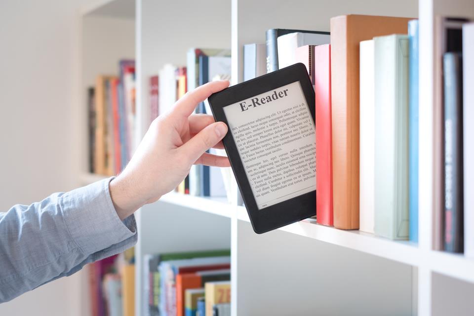 Mężczyzna wyjmujący czytnik e-booków z półki z książkami.