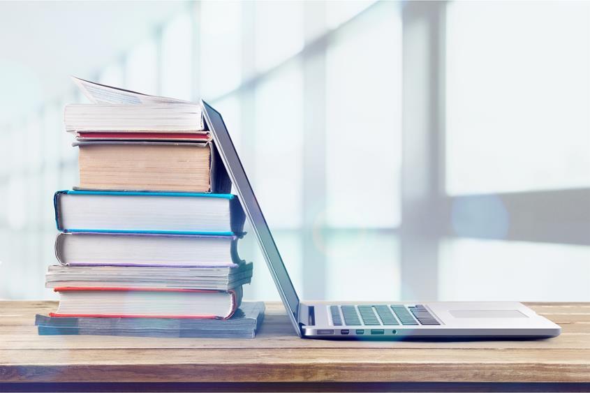 Otwarty laptop oparty o stos ułożony z książek.