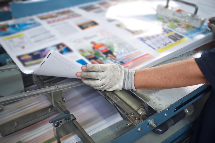Drukarz w trakcie drukowania materia³ów poligraficznych w parku maszynowym drukarni.