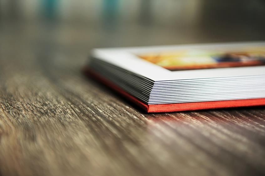 Otwarta ksiąźka leżąca na stole z zadrukowaną stroną ze zdjęciem