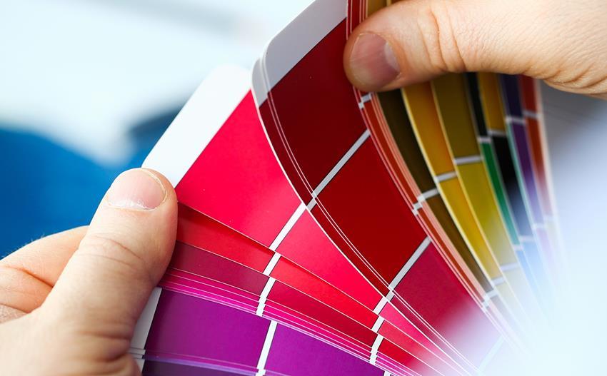 Wybór wzorników kolorów. Paleta kolorystyczna trzymana w dłoniach.