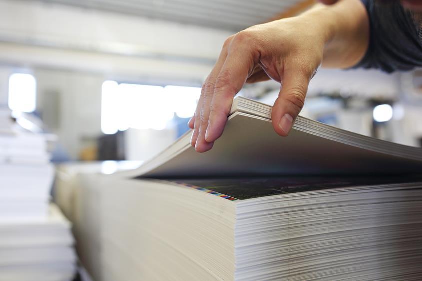Ryzy papieru po wydruku ułożone w stos.