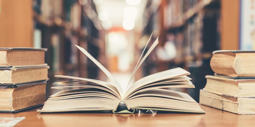 Otwarta książka na stole na tle półek w bibliotece.