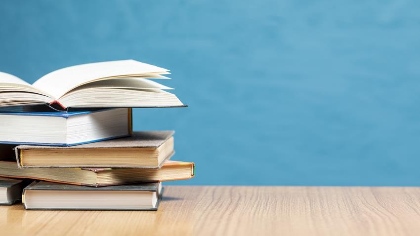 Stos poukładany z książek leżących na biurku.
