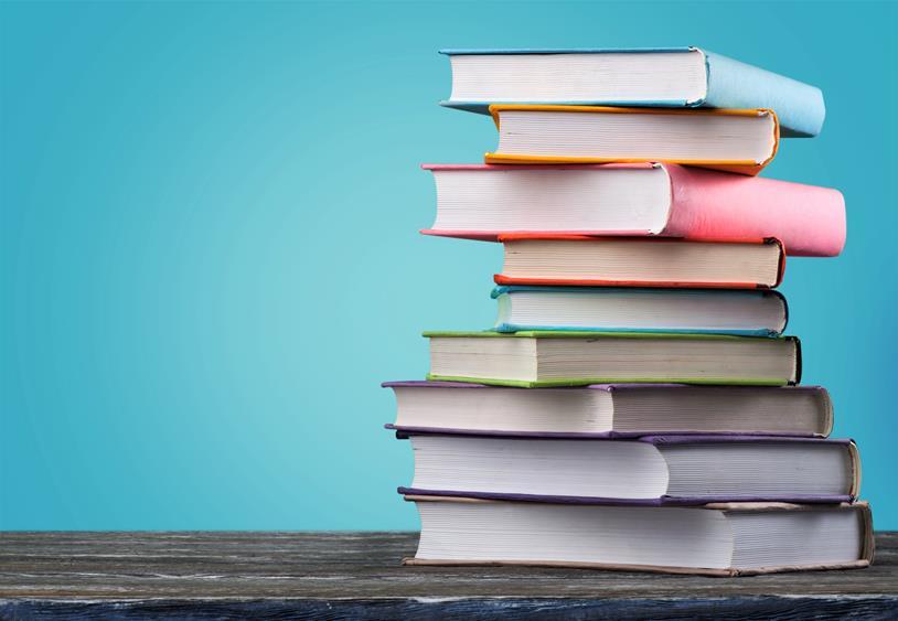 Zamknięte książki ułożone w stosie na biurku.