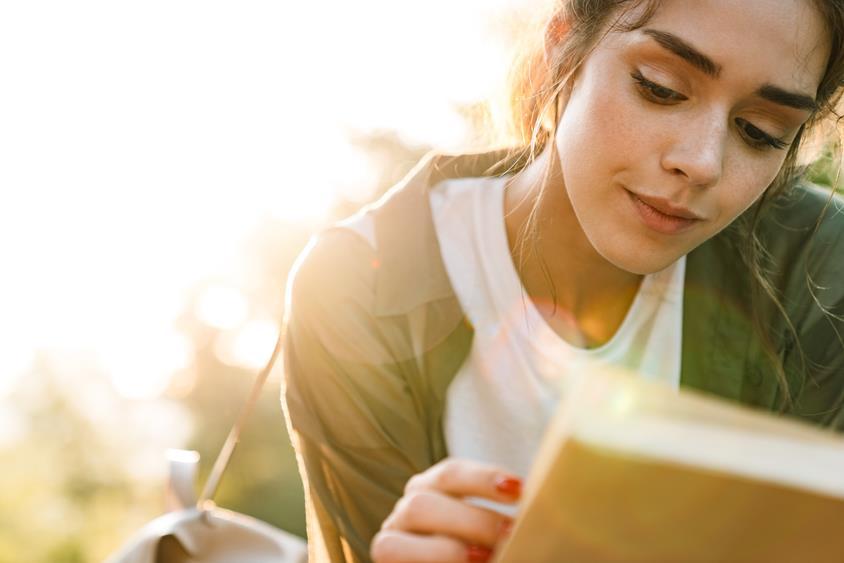 Młoda kobieta czytająca książkę na świeżym powietrzu.