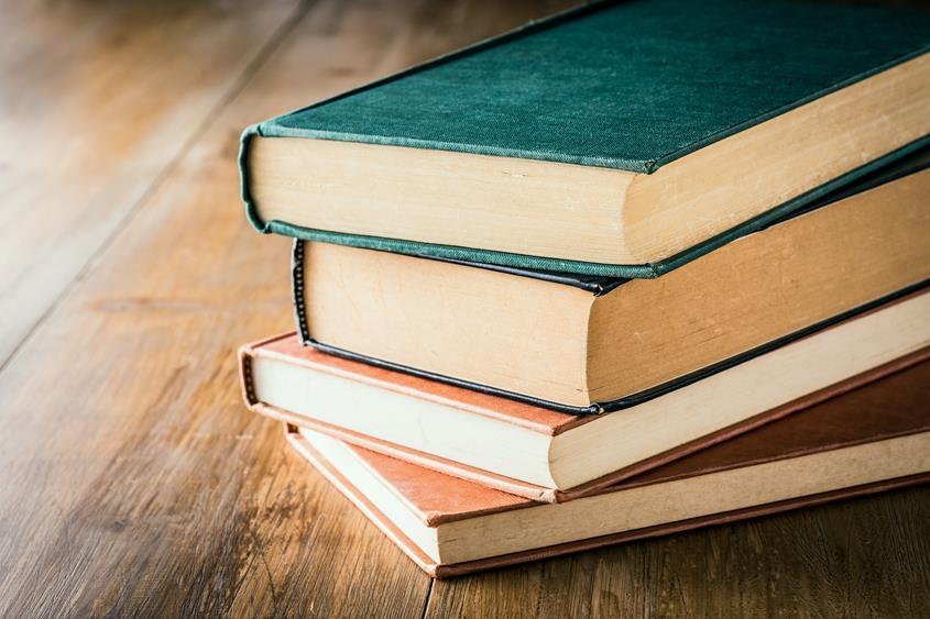 Książki w okładkach vintage ułożone jedna na drugiej na drewnianym biurku.